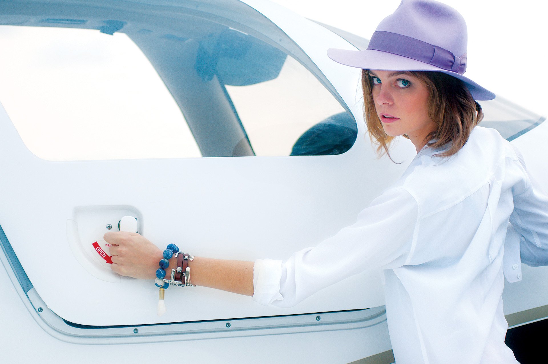 Fashion photography of a model opening an airplane cockpit at the Athens, Ga airport.